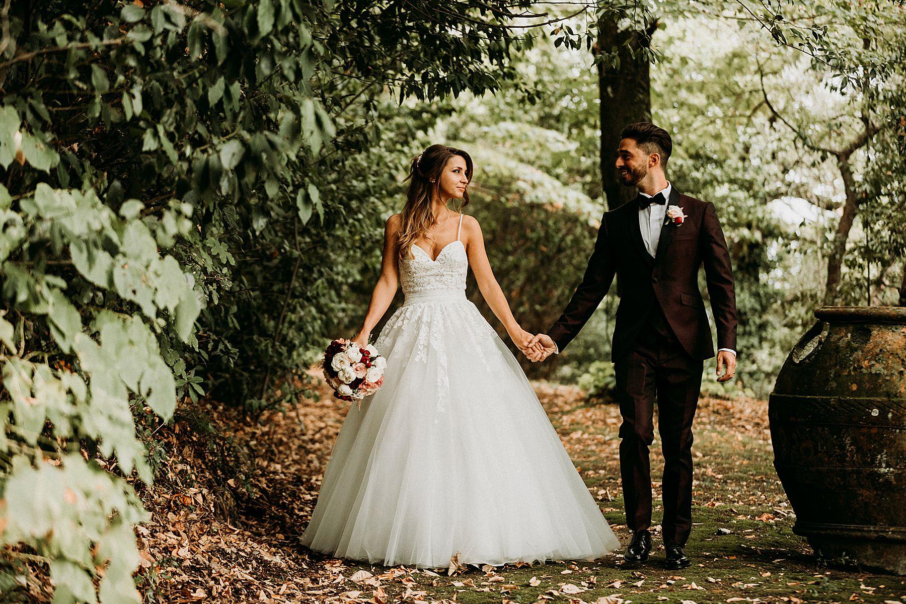 Sposo e sposa mano nella mano nel giardino di Villa di Montefiano a Fiesole