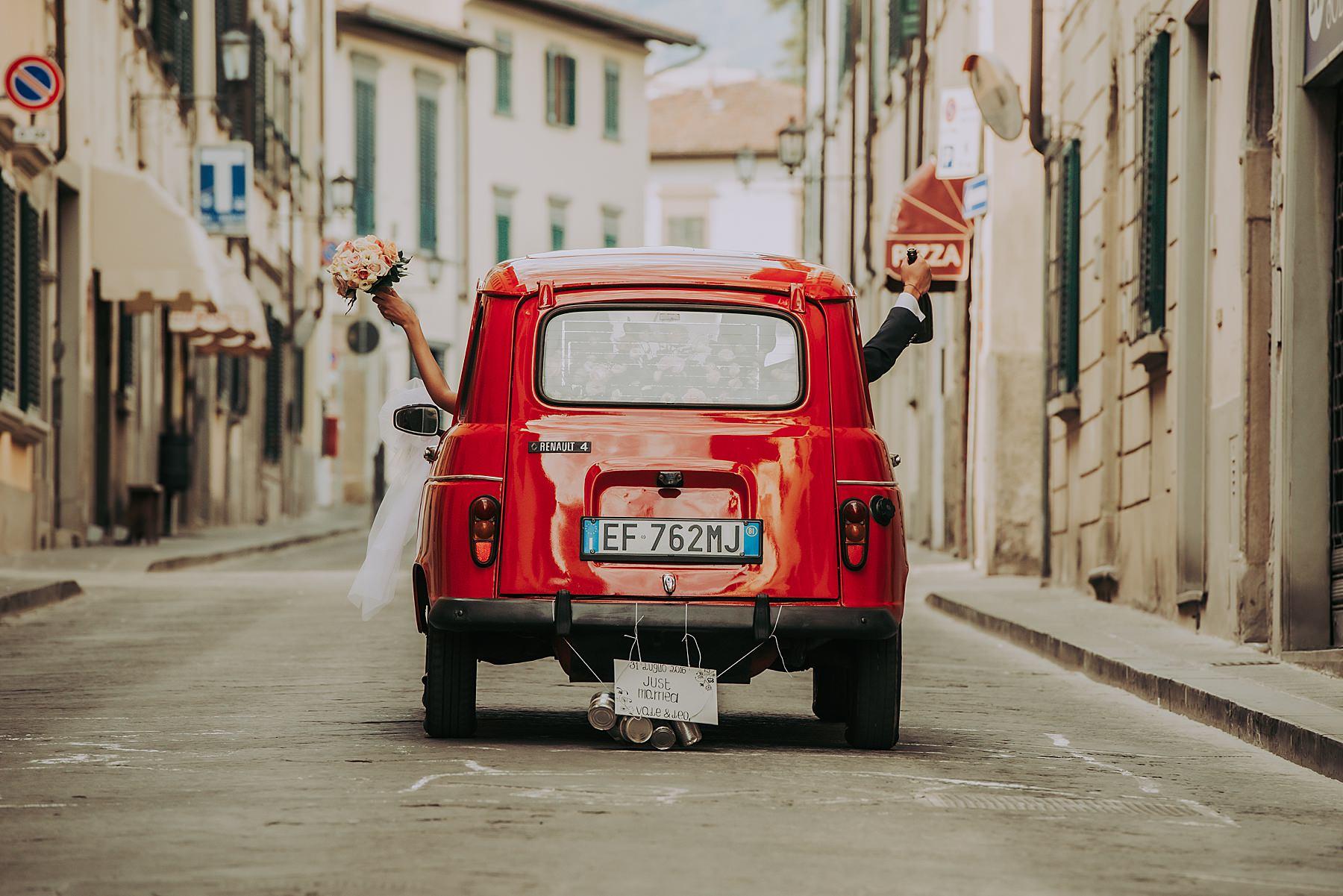 Matrimonio macchina sposi barattoli legati dietro auto