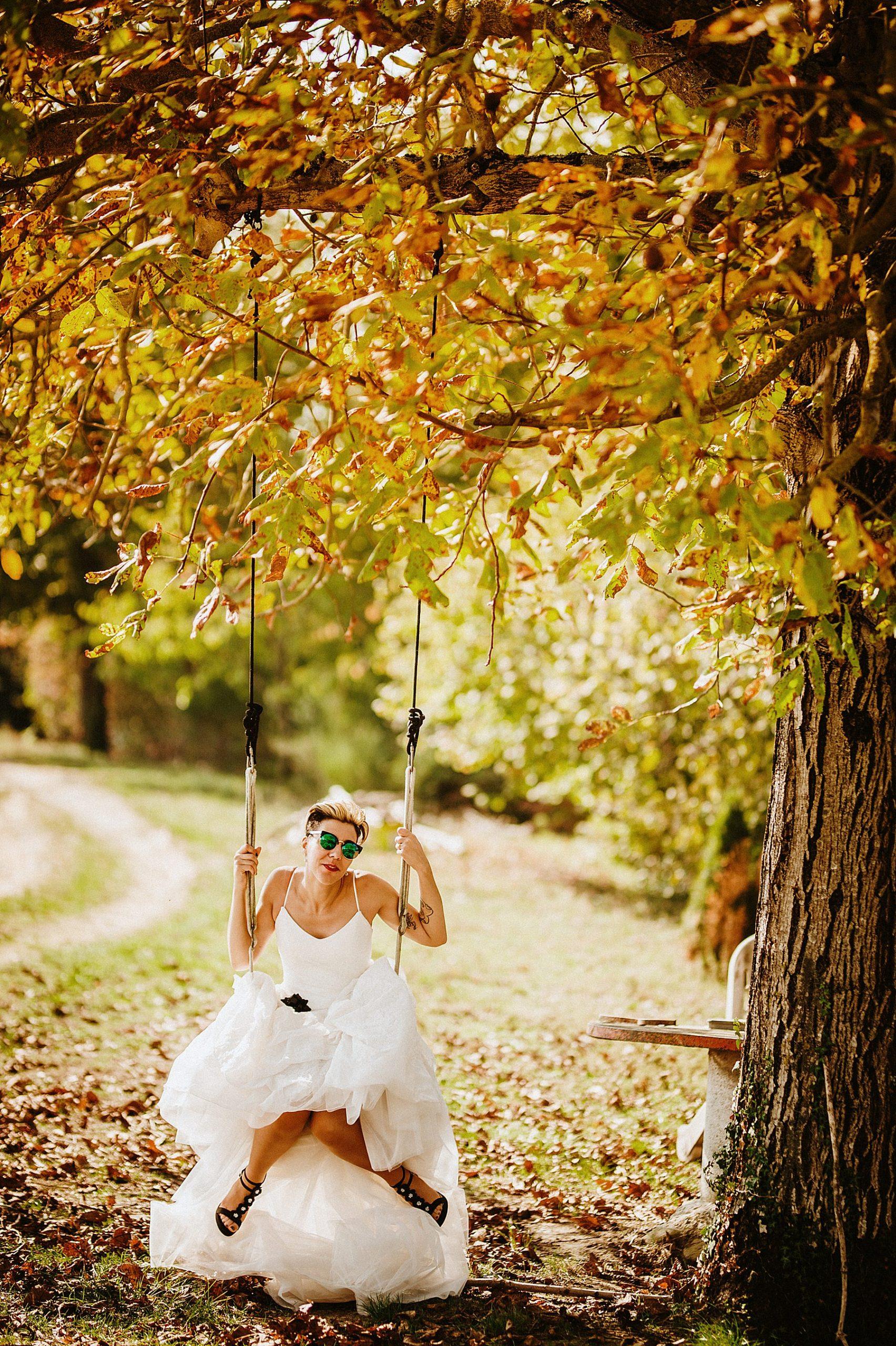 bellissima sposa su altalena sotto l'albero in autunno