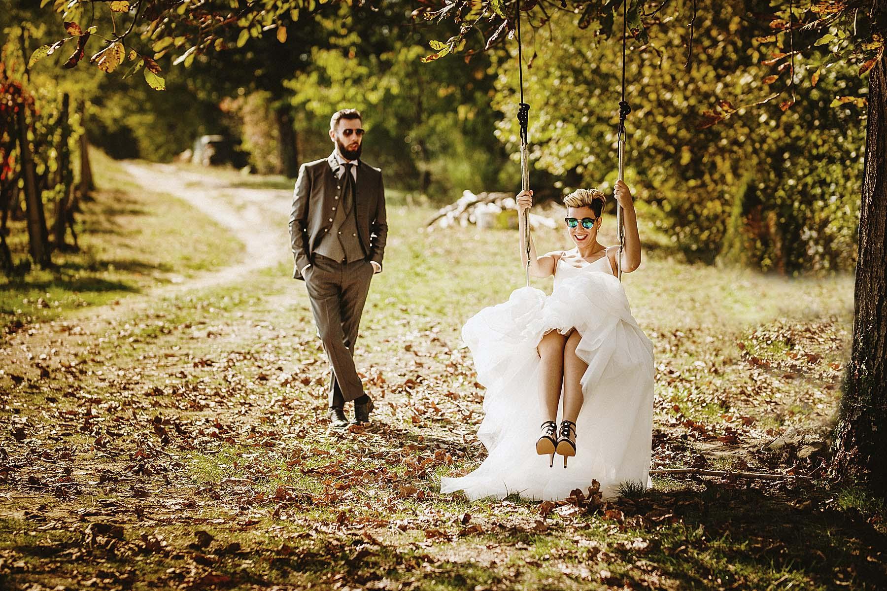 sposa su altalena sotto l'albero in autunno con sposo che la guarda