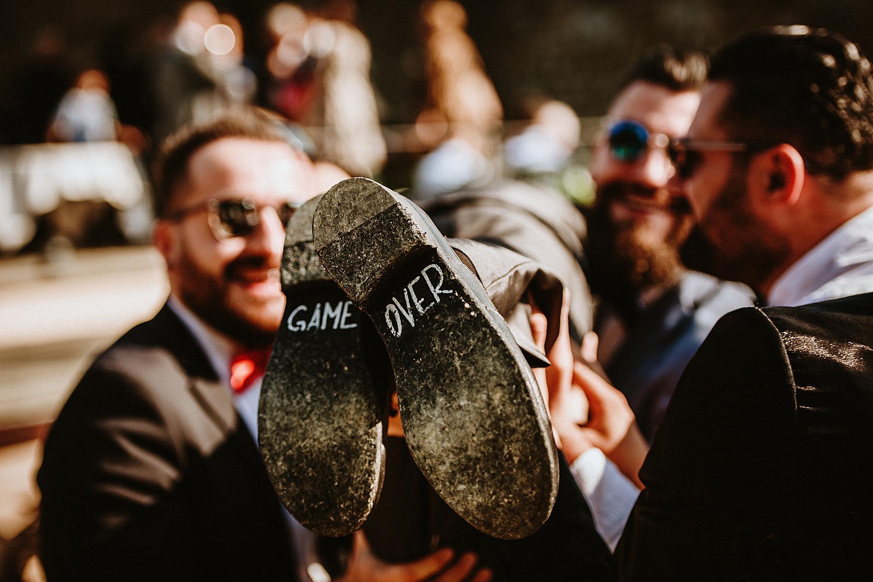 Scritta game over su suole scarpe dello sposo