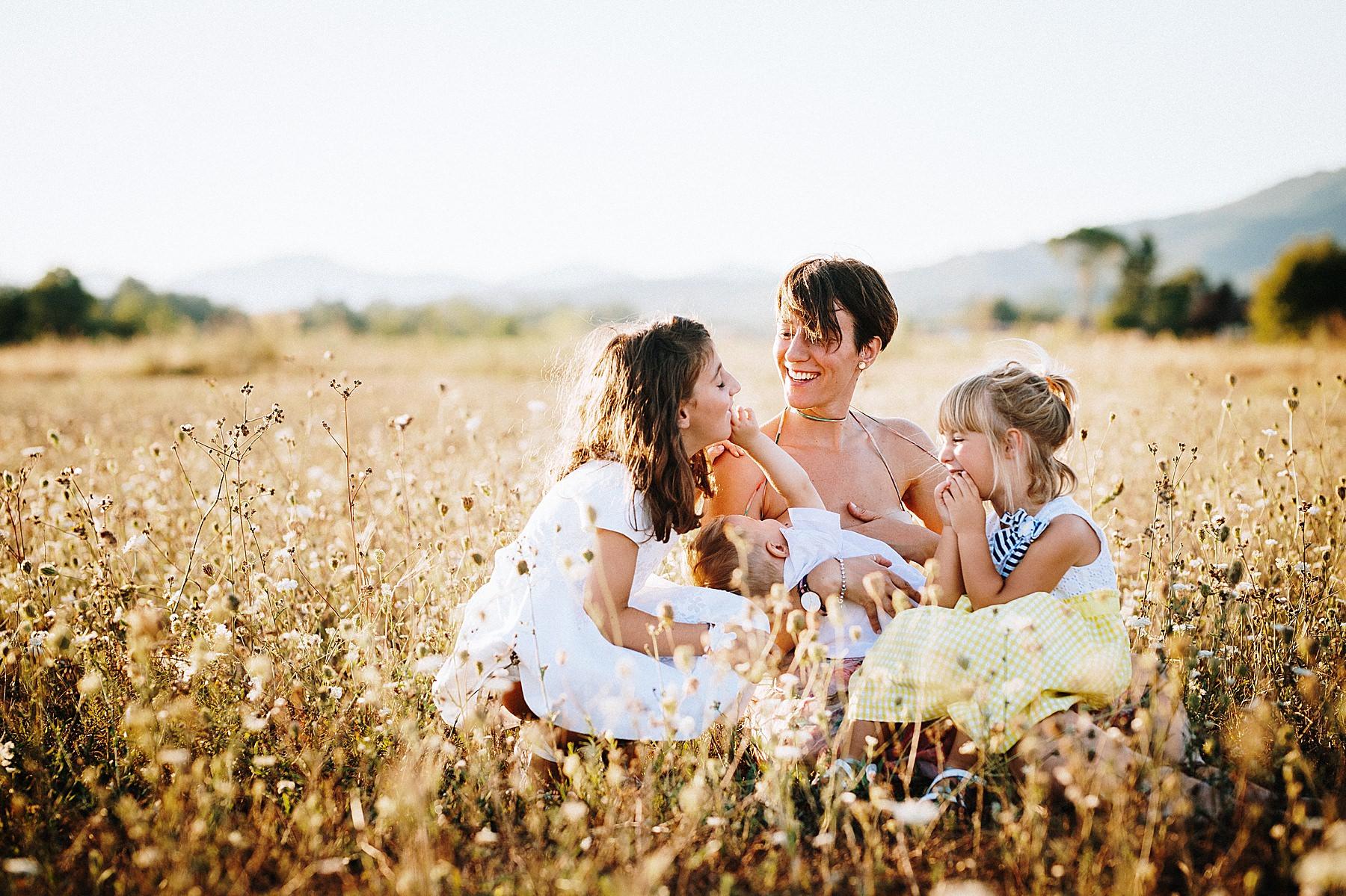 Servizio fotografico di famiglia nel Mugello allattare all'aperto nei campi