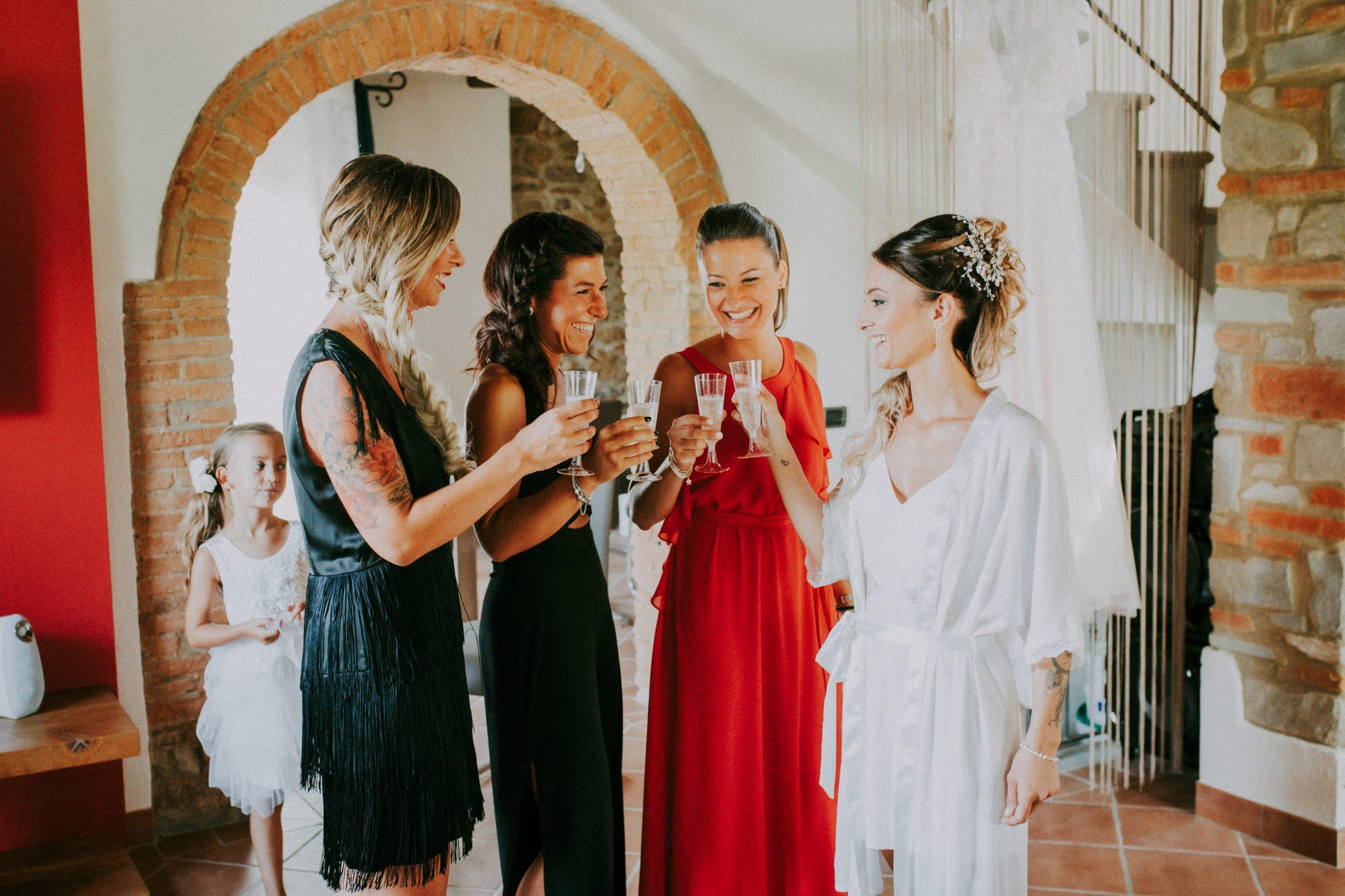 sposa che brinda con le amiche durante la preparazione