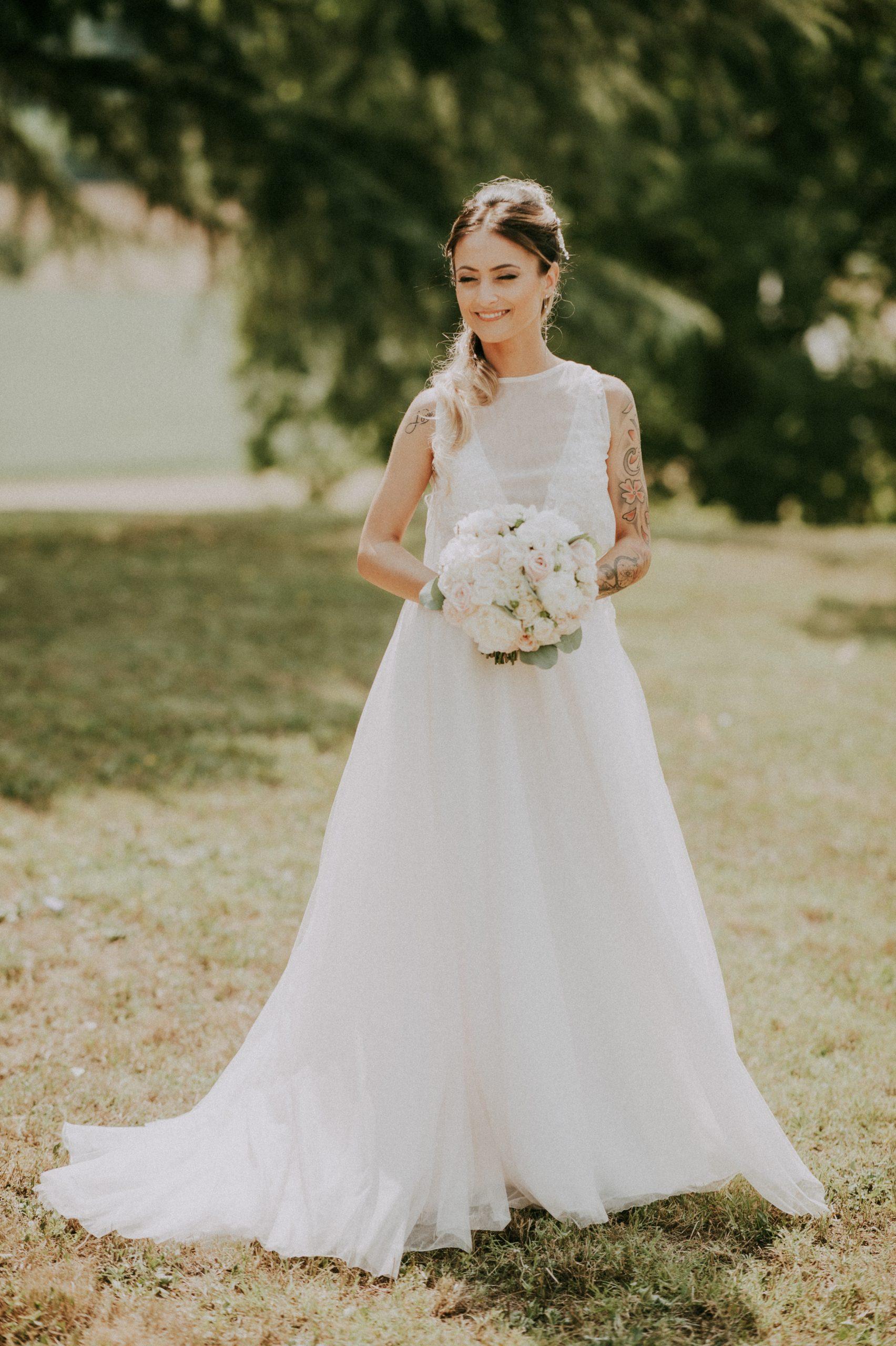 bellissima sposa con abito e braccia tatuate scoperte