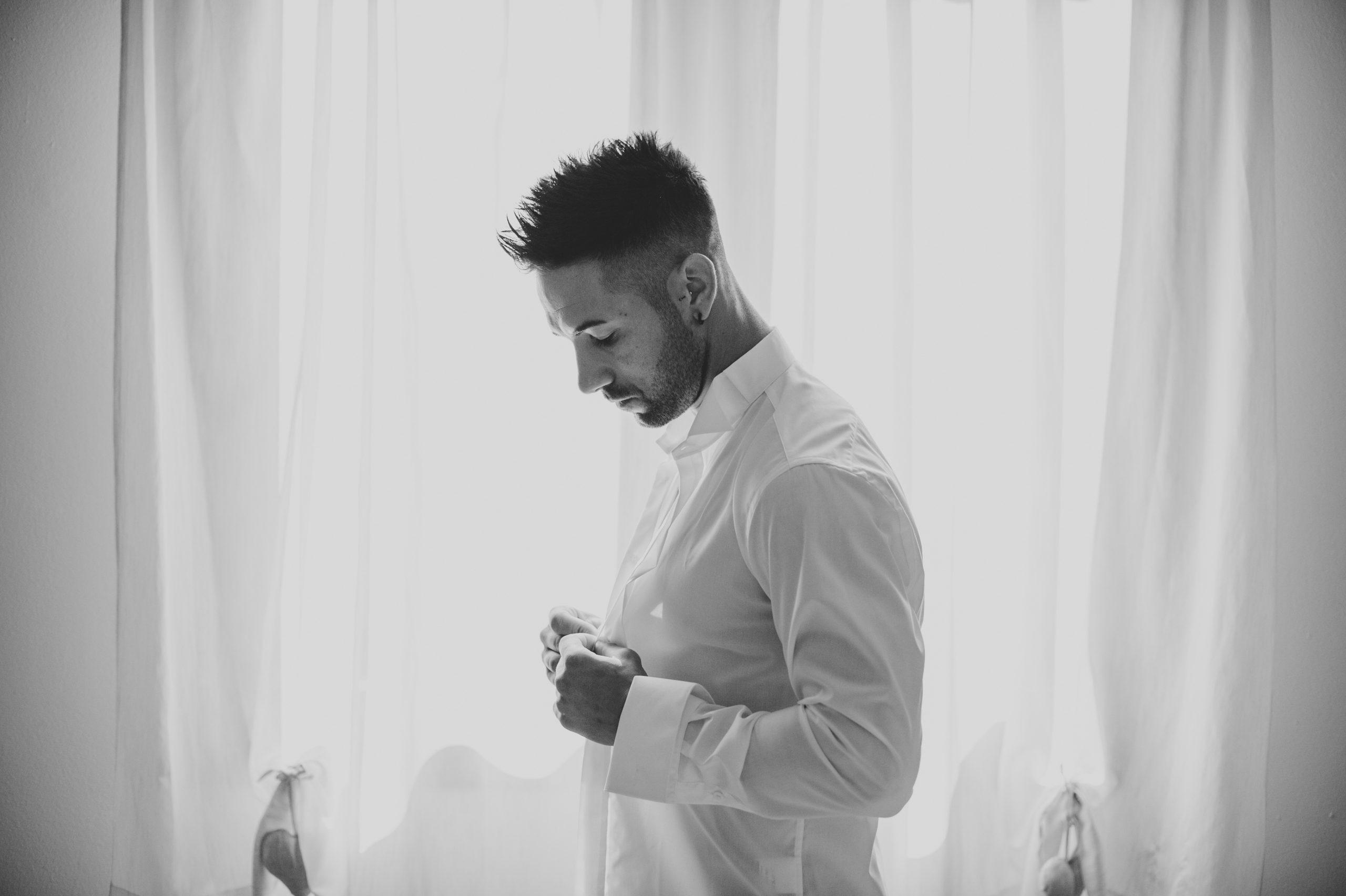 sposo che si abbottona la camicia con una bellissima luce davanti alla finestra