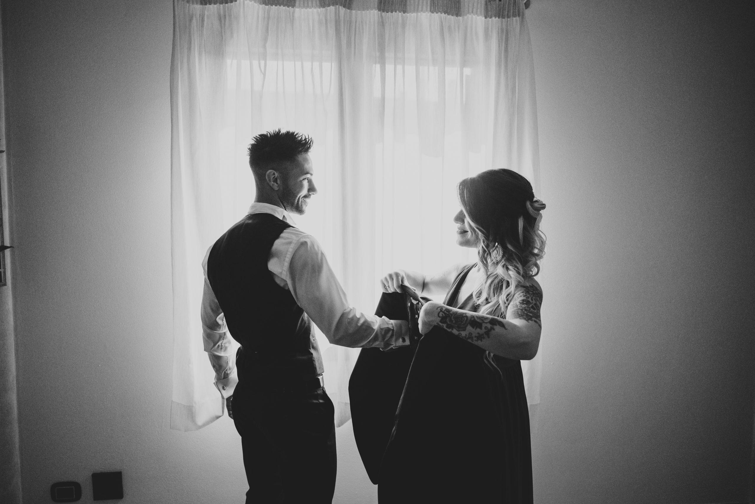 foto in bianco e nero dello sorella sposo che aiuta lo sposo a vestirsi