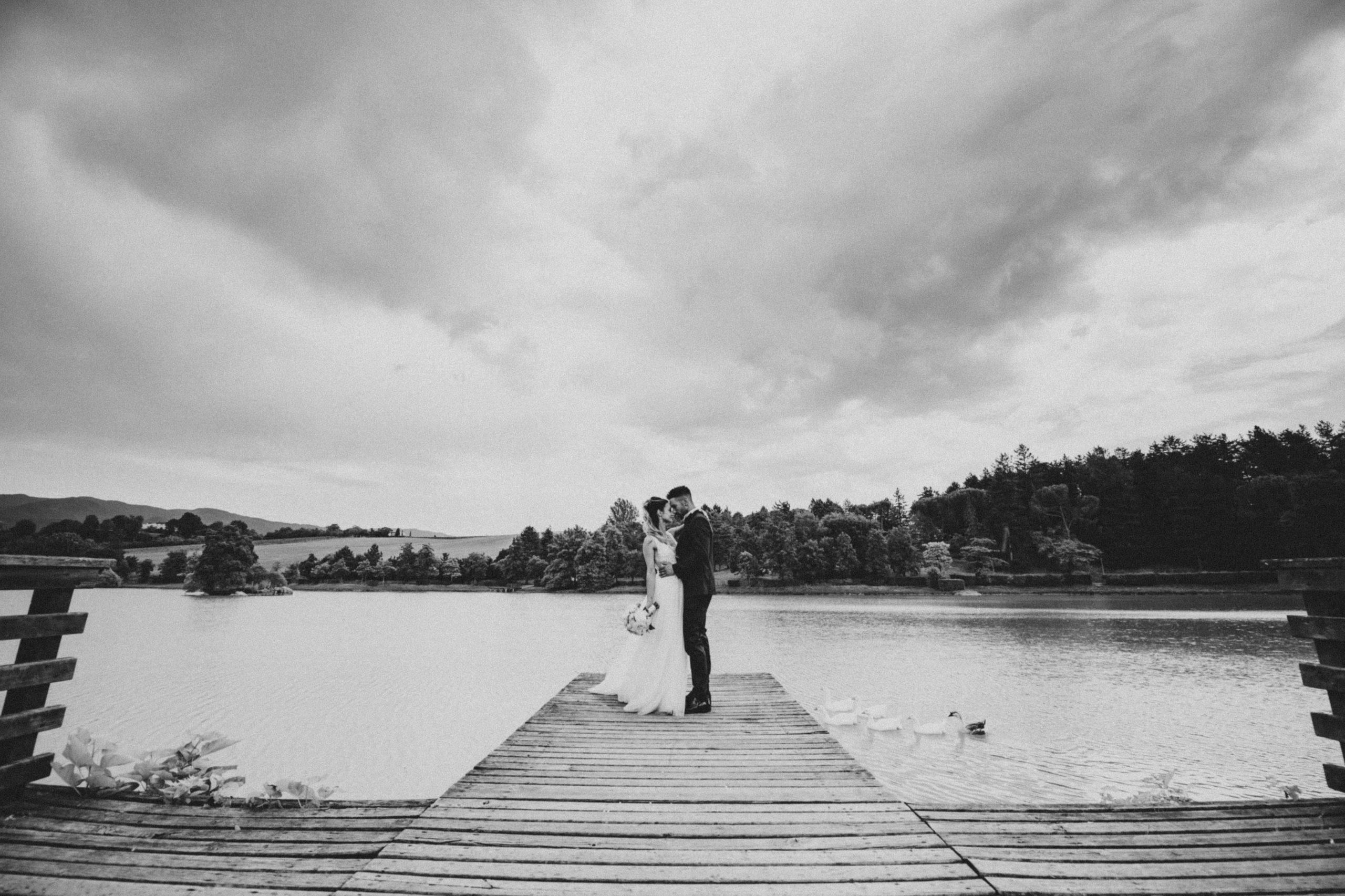 bellissima foto in bianco e nero degli sposi al lago di Montelleri a Vicchio nel Mugello mentre passano le papere
