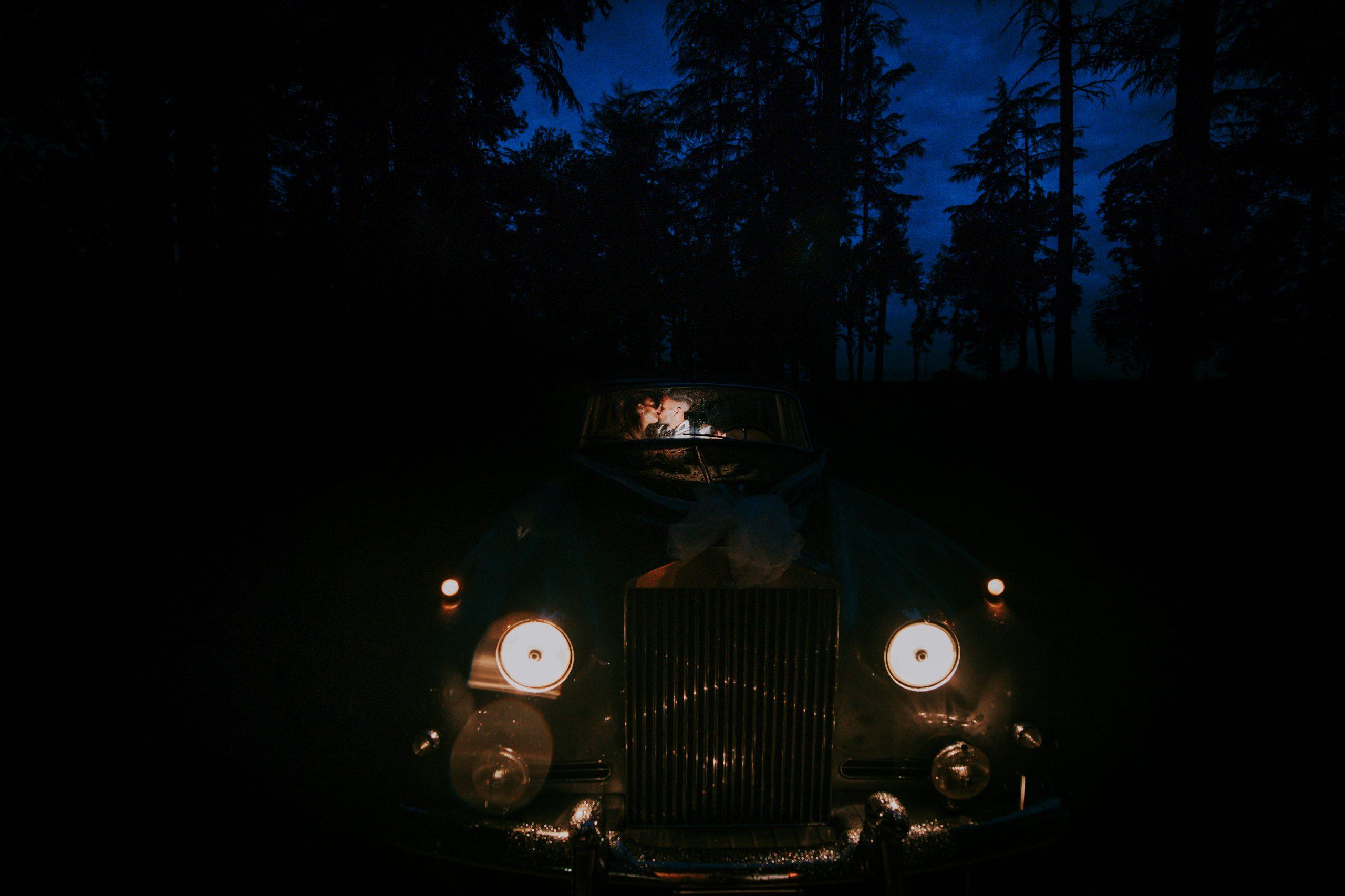 Foto degli sposi in auto d'epoca di notte a Villa di Corte